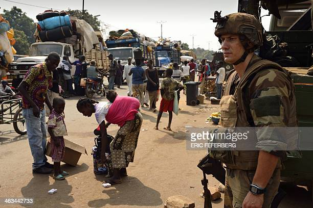 A French soldier from the Sangaris Operation stands guard as Muslim civilians prepare to board trucks in the P12 district of Bangui to flee the...