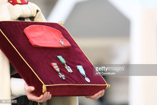 A French soldier holds the military decorations of late French WWII colonel Fred Moore including the Croix de guerre 19391945 the Croix de l'ordre de...
