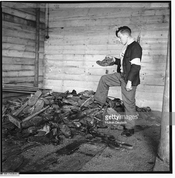 French soldier investigates the pile of footwear belonging to victims near the crematorium at Struthof Concentration Camp. | Location: Struthof Camp,...