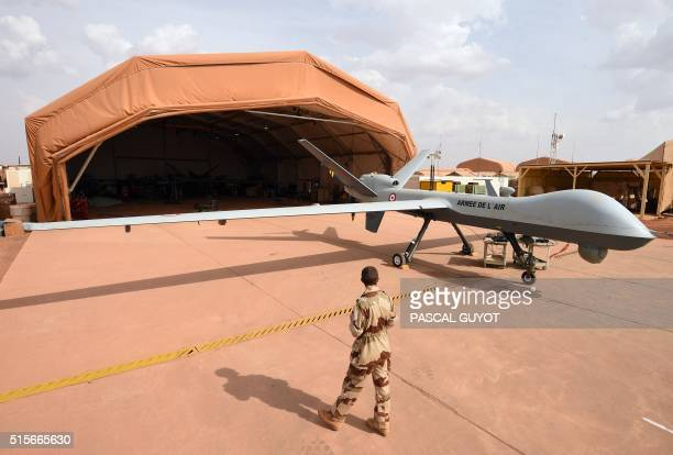 A French soldier involved in the regional antiinsurgent Operation Barkhane stands guard next to a Reaper drone at the French military airbase in...