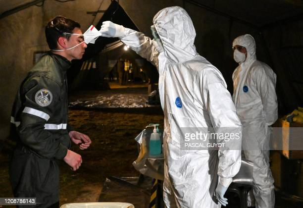 A French soldier is being decontaminated after getting out of an Airbus A320 medicalized by the French army upon their arrival from a a mission in...