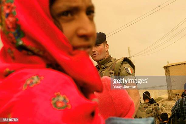 French soldier looks past a young afghan woman on April 29 2004 in Kabul Afghanistan