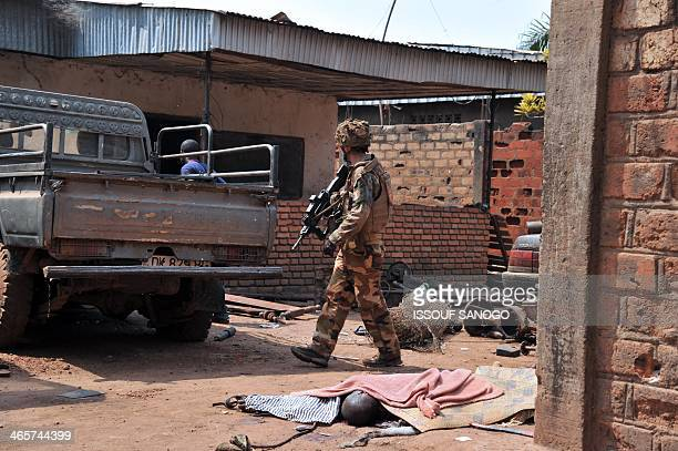 French soldier of Operation Sangaris walks past the body of a Muslim man killed by Christian Anti-Balaka combattants as he patrols in Bangui on...