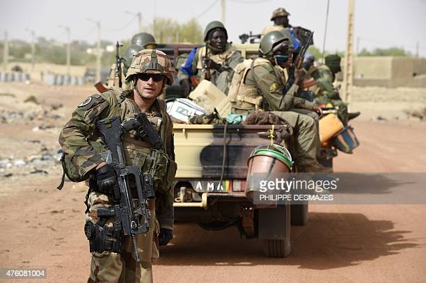 A French soldier of the 93 th Regiment d'Artillerie de Montagne stands next to Malian soldiers on June 4 at Goundam 80 km east of Timbuktu central...