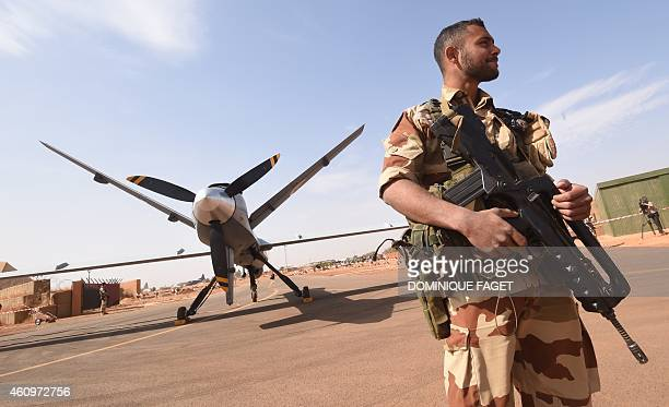 A French soldier of the aerial detachment of the Operation Barkhane stands guard near a Reaper drone at the Nigerian military airport Diori Hamani in...