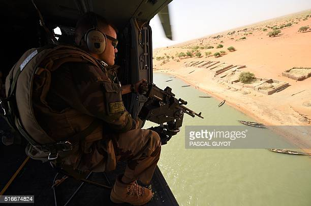 A French soldier of the operation Barkhane an antiterrorist mission in Sahel patrols during a tactical flight on March 12 2016 over Mali France's...