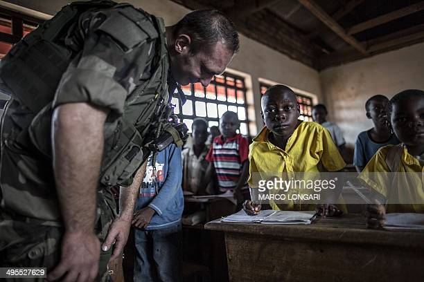 A French soldier of the Sangaris contingent bends down to look at a studen'ts work as he pays a visit to a school in the formerly Muslim PK12...