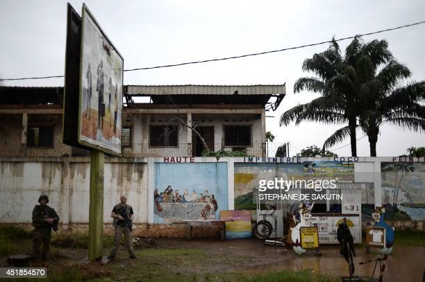 A French soldier of the Sangaris force stands guard on July 8 2014 at the entrance of the PK5 muslim area of Bangui French Defence minister JeanYves...