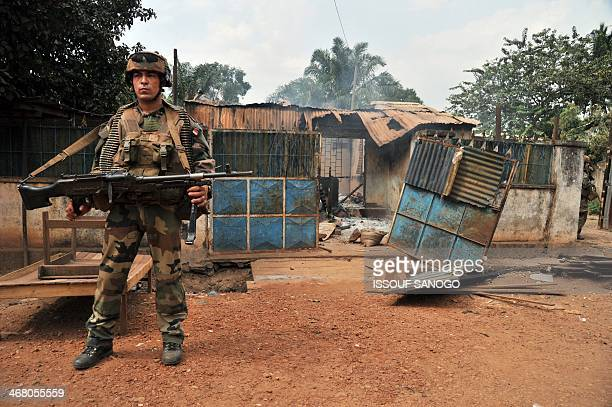 French soldier of the Sangaris military operation stands in front of a burned house in the 5th district of Bangui on February 9, 2014. According to...