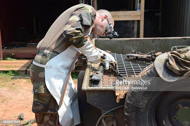 "French soldier of the Sangaris operation takes weapons apart on december 4, 2014 in Bangui. The French military operation called ""Sangaris"" was..."