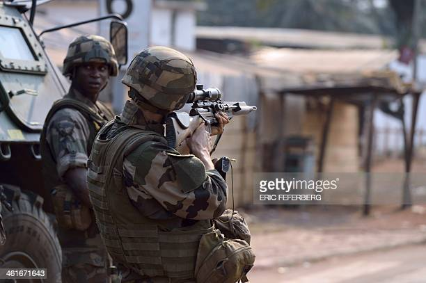 A French soldier part of the Sangaris operation forces aims rifle during a patrol at the Reconciliation crossroad as unidentified shotguns fired in...