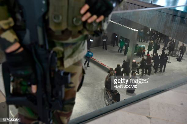 French soldier patrols inside the arrival terminal of the Charles de Gaulle Airport in Roissy, northeast of Paris, on March 23 a day after triple...