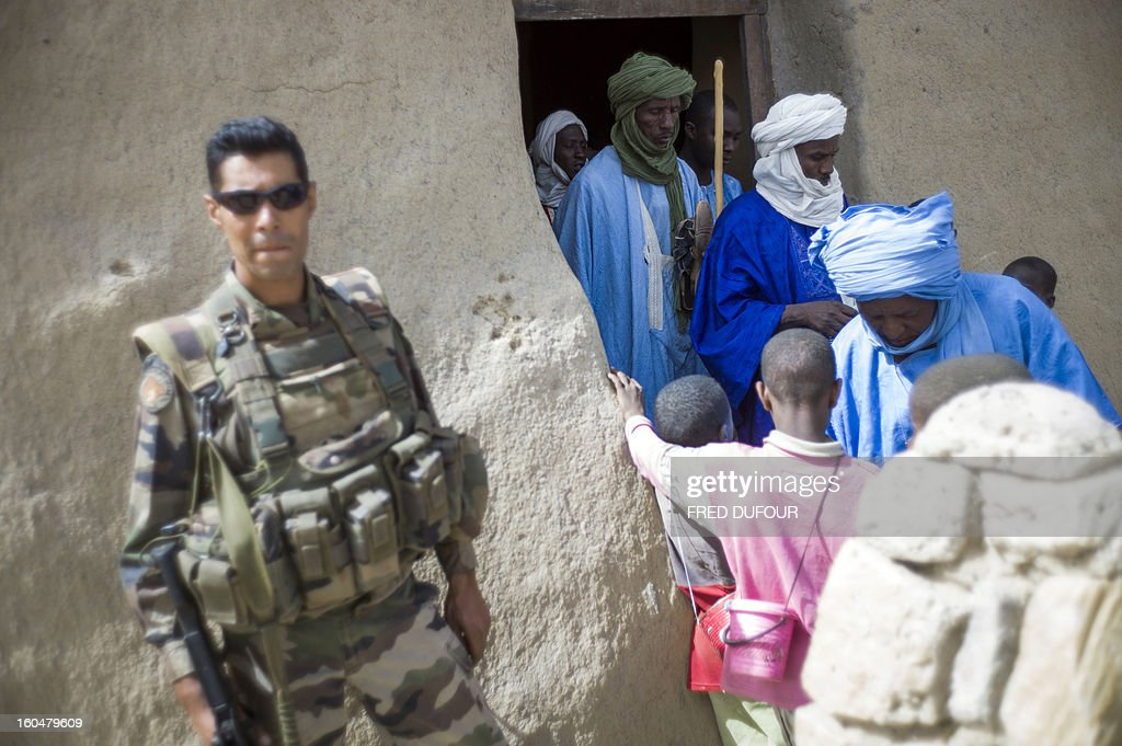 A French soldier stands as people walk out of the Djingareyber mosque after the prayer in Timbuktu on February 1, 2013. The fabled desert city of Timbuktu, an ancient centre of Islamic learning, has been recaptured on January 28 by French-led forces in their offensive against Islamist rebels who have been occupying Mali's north since last April.