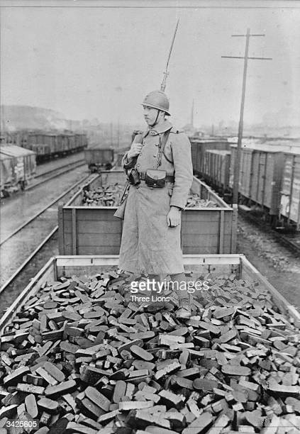French soldier stands on a trainload of coke near Cologne The shipment is part of the reparations paid to the French in coal and coke by Germany...
