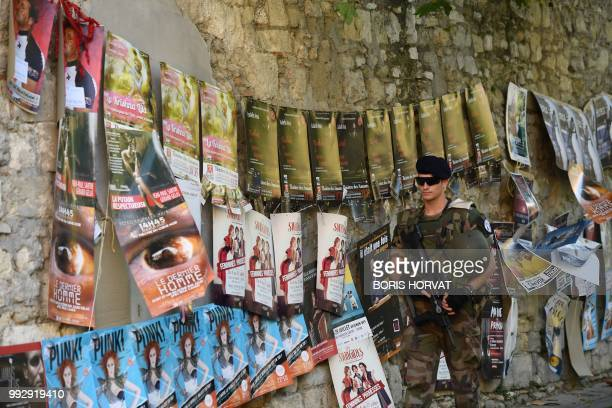 A French soldier walks past posters advertising plays as he patrols in a street of Avignon southeastern France on July 6 2018 on the first day of the...