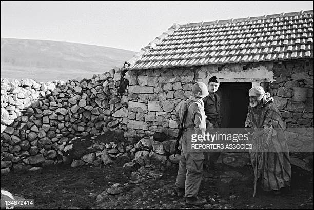 French soldiers and a civilian in front of a house during 'Operation Bigeard' in March 1956 when an armed outbreak in SoukAhras South of Constantine...