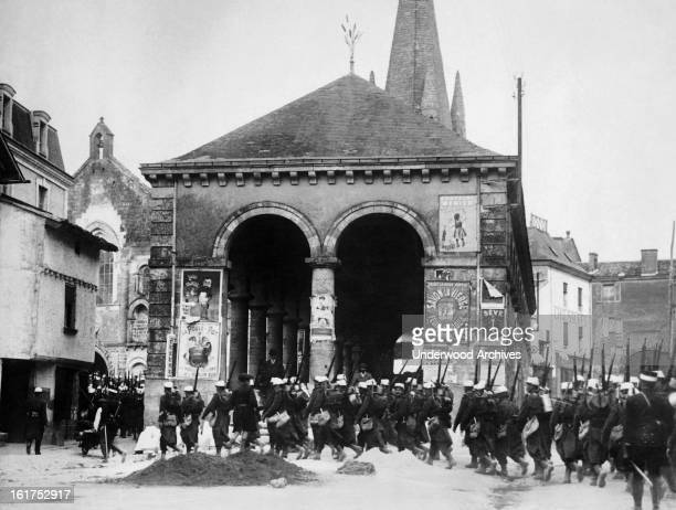 French soldiers are marching past a German spy sign Paris France August 15 1914 The poster at the left of the building advertising the German soup La...