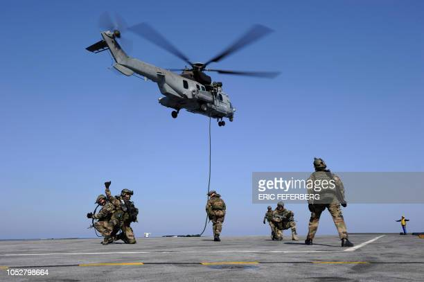 French soldiers are winched down from a Caracal helicopter during a training on March 25 on the French aircraft carrier Charles De Gaulle during the...