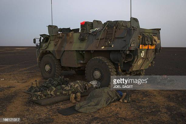 French soldiers from the 126th Regiment Infantery sleep near an armoured personnel carrier early in the morning on April 8 2013 some 105 kilometers...