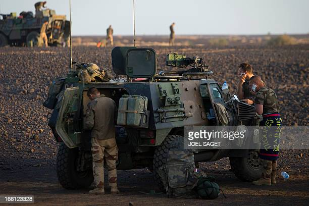 French soldiers from the 126th Regiment Infantery stand near an armoured personnel carrier early in the morning on April 8 2013 some 105 kilometers...