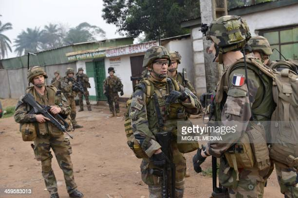 French soldiers from the 1er Regiment Chasseurs Parachutistes taking part in the Sangaris operation patrol the Fouh district in Bangui on December 28...