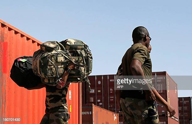French soldiers from the 92eme Regiment d'Infanterie of the French Army battlegroup Wild Geese carry backpack and equipments to load them into a...