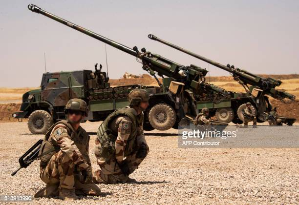 French soldiers from the Wagram Task Force kneel next to a unit of CAESAR a French selfpropelled 155 mm howitzer north of Mosul on July 13 as the...