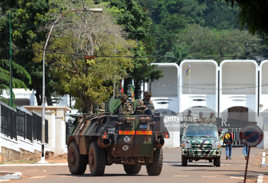 French soldiers in an armored vehicle pass ex-Seleka rebels in truck as they patrol in front of the presidential palace in Bangui on December 8, 2013. French troops poured into the impoverished landlocked country on December 7 after President Francois Hollande announced he was boosting a UN-mandated French force to 1,600 soldiers. French Foreign Minister Laurent Fabius said on December 8 that nearly 400 people were killed in the last three days in violence in the Central African Republic capital Bangui, but that calm had returned.