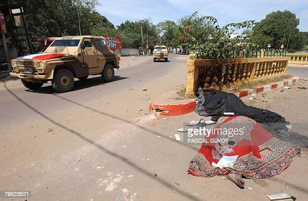 French soldiers in armoured vehicles drive past blanketcovered bodies in the capital city N'Djamena on February 05 2008 after violent fighting Rebels...