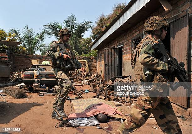 French soldiers of Operation Sangaris walk past the body of a Muslim man killed by Christian Anti-Balaka combattants as they patrol in Bangui on...