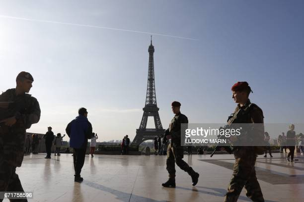 TOPSHOT French soldiers of the 'Operation Sentinelle' patrol on the Human Right square in front of the Eiffel tower in Paris on April 23 as France...