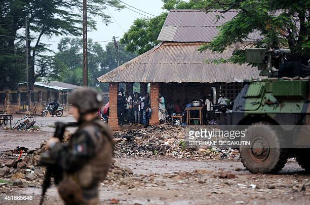 French soldiers of the Sangaris force patrol as locals take shelter from the rain on July 8, 2014 in the Fatima area of Bangui. French Defence...