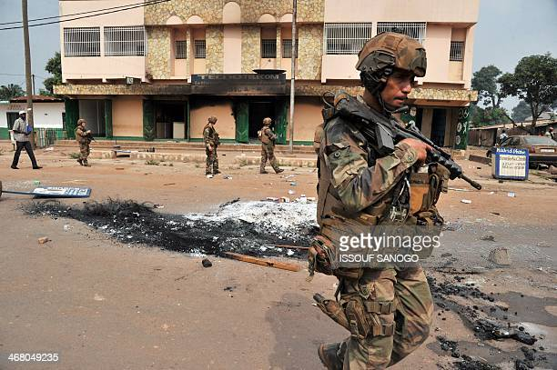 French soldiers of the Sangaris military operation walk past ashes on February 9 2014 in the 5th district of Bangui where a man was killed and burned...