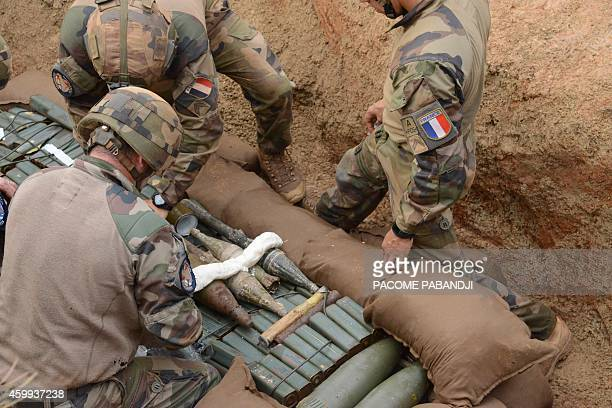 French soldiers of the Sangaris operation lay explosive onto weapons and explosive devices before destroying them, in Bangui on december 4, 2014 in...