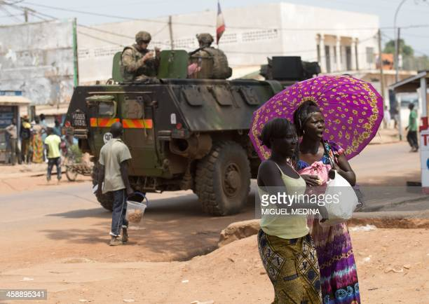 French soldiers part of the operation Sangaris sit on a armored vehicle as women holding an umbrella walk by at the Yagato district on December 22...