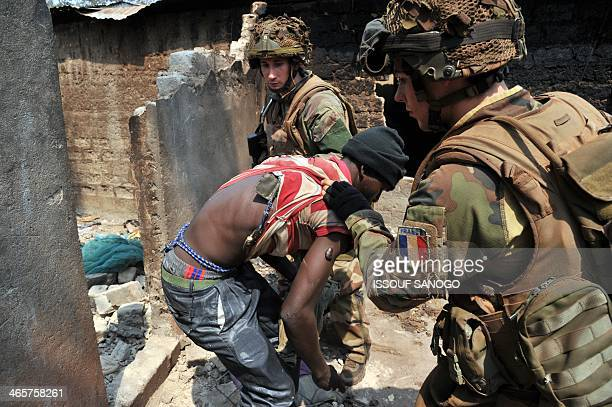 French soldiers part of the Sangaris operation search a man during a patrol in Bangui on January 29 2014 Sporadic gunfire loud explosions and street...