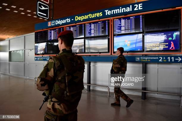 French soldiers patrol inside the departure terminal of the Charles de Gaulle Airport in Roissy northeast of Paris on March 23 a day after triple...