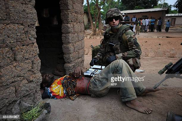 French soldiers provide first aid to a man suffering from gunshot wounds during a disarmament operation in Bangui on December 9 2013 French troops on...