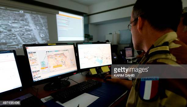 French soldiers sit in a control room at a French military base at an undisclosed location in the Gulf on November 17 as they monitor operations...