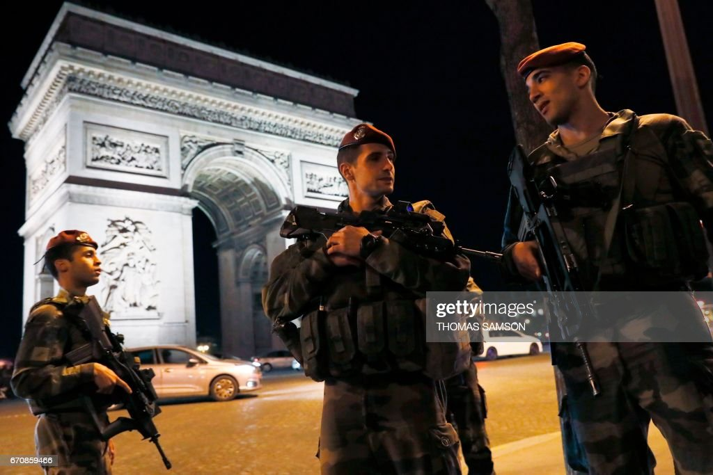 TOPSHOT - French soldiers stand guard at the Arc de Triomphe near the Champs Elysees in Paris after a shooting on April 20, 2017. One police officer was killed and another wounded today in a shooting on Paris's Champs Elysees, police said just days ahead of France's presidential election. France's interior ministry said the attacker was killed in the incident on the world famous boulevard that is popular with tourists. SAMSON
