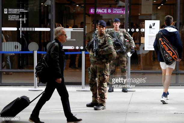 French soldiers stand guard at the entrance of the train station Gare Montparnasse in Paris on October 2 2017 as part of the Sentinelle military...