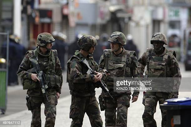French soldiers stand guard in the northern Paris suburb of SaintDenis city center on November 18 as French Police special forces raid an appartment...