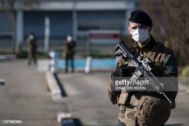 French soldiers stand guard the construction site of the military field hospital at The Emile Muller Hospital in Mulhouse, eastern France, on March...