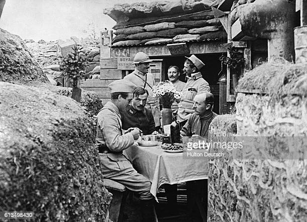 French soldiers take advantage of a peaceful moment on the Western Front to have a meal complete with flowers and a bottle of wine during the World...