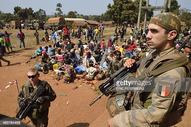French soldiers taking part in 'Operation Sangaris' stand guard as Muslim people wait to seek refuge at the Boali church on January 19 in Boali some...