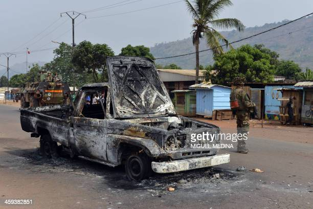 French soldiers taking part in the Sangaris operation are pictured next to a burnt pickup vehicle belonging to Chadian soldiers part of the MISCA in...