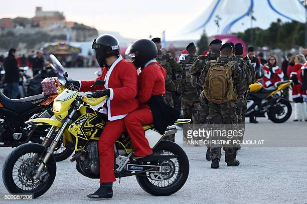 French soldiers walk past bikers dressed as Santa Claus as they patrol in front of MUCEM on December 20 2015 in Marseille southern France as part of...