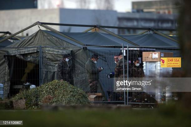 French soldiers wearing protective masks set up tents as part of a field hospital to cope with a surge in COVID-19 cases on March 22, 2020 in...