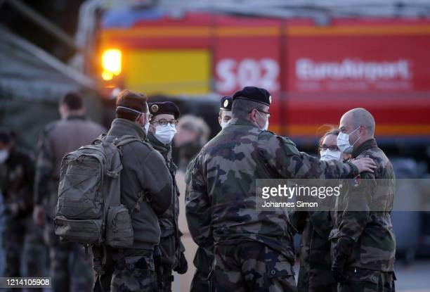 French soldiers wearing protective masks talk before setting up tents as part of a field hospital to cope with a surge in COVID-19 cases on March 22,...