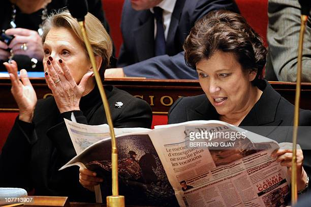French Solidarity and Social Cohesion Minister Roselyne Bachelot reads Le Monde newspaper near Foreign Affairs minister Michele AlliotMarie during...
